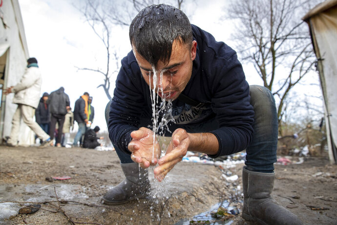 A migrant washes his face at the Vucjak refugee camp outside Bihac, northwestern Bosnia, Friday, Dec. 6, 2019. Despite calls for their relocation before winter, hundreds of migrants remain stuck at a make-shift tent camp in northwestern Bosnia. (AP Photo/Darko Bandic)