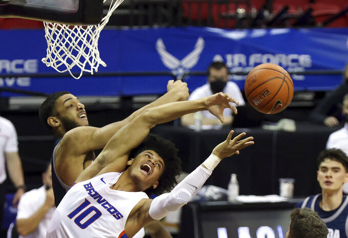 Nevada forward Robby Robinson, left, and Boise State guard RayJ Dennis (10) reach for a rebound during the first half of an NCAA college basketball game in the quarterfinals of the Mountain West Conference men's tournament Thursday, March 11, 2021, in Las Vegas. (AP Photo/Isaac Brekken)