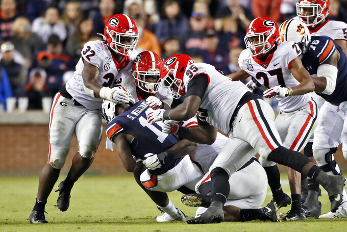 Georgia defenders, including linebacker Monty Rice (32), defensive lineman Devonte Wyatt (95), defensive back Eric Stokes (27) and linebacker Tae Crowder (30) swarm Auburn wide receiver Shedrick Jackson (11) during an NCAA college football game, Saturday, Nov. 16, 2019, in Auburn, Ala. Georgia won 21-14. (Bob Andres/Atlanta Journal-Constitution via AP)