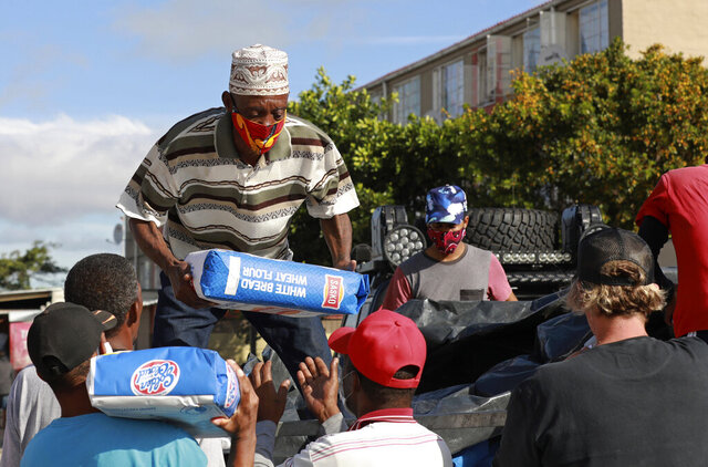 In this May 2, 2020, photo, Danny, a senior member of the Hard Livings gang, helps distribute food with rival gang members in Manenberg neighborhood in Cape Town, South Africa. The gangs are working together, under the direction of a preacher, to deliver bread, flour and vegetables to poor families who are struggling during South Africa's coronavirus lockdown. (AP Photo/Nardus Engelbrecht)