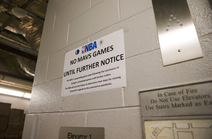 In this Wednesday, March 11, 2020  photo, a sign is posted at an elevator on the event level at American Airlines Arena, home of the Dallas Mavericks NBA basketball team, in Dallas, after the league announced it is suspending its season indefinitely in response to the coronavirus. (Ashley Landis/The Dallas Morning News via AP)