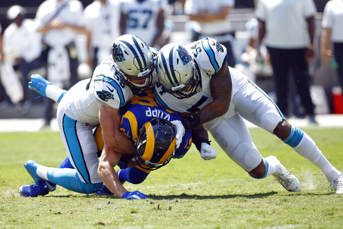 Carolina Panthers middle linebacker Luke Kuechly, left, and outside linebacker Shaq Thompson (54) tackle Los Angeles Rams wide receiver Cooper Kupp (18) during the first half an NFL football game in Charlotte, N.C., Sunday, Sept. 8, 2019. (AP Photo/Brian Blanco)