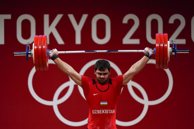 Akbar Djuraev of Uzbekistan competes in the men's 109kg weightlifting event at the 2020 Summer Olympics, Tuesday, Aug. 3, 2021, in Tokyo, Japan. (AP Photo/Seth Wenig)