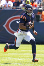 Chicago Bears quarterback Justin Fields (1) runs with the ball against the Miami Dolphins during the second half of an NFL preseason football game in Chicago, Saturday, Aug. 14, 2021. (AP Photo/Nam Y. Huh)