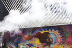 Steam blows by a mural placed at the future site of 2 World Trade Center, a planned commercial office tower, Monday, Sept. 9, 2019 in New York. In the background is the World Trade Center transportation hub. Wednesday marks the 18th anniversary of the attacks of Sept. 11, 2001. (AP Photo/Mark Lennihan)