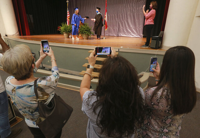 Family members watch Carmen Antillon receives her Tupelo High School diploma from Tupelo High School 12th grade Assistant Principal L.V. McNeal during a graduation ceremony at Milam Elementary School, Wednesday, May 6, 2020, in Tupelo Miss. The school district divided up the graduation ceremony to five different locations over three days with no more than four guests in attendance. (Thomas Wells/The Northeast Mississippi Daily Journal via AP)