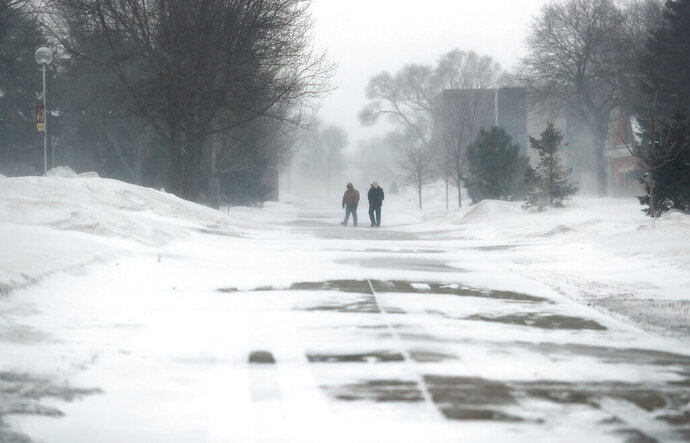In this Wednesday, Feb. 12, 2020, photo, a pair of pedestrians make their way across campus at Northern State University in blowing snow in the morning, in Aberdeen, S.D. A wind chill warning is in effect Thursday for northeastern North Dakota and northern Minnesota. (John Davis/Aberdeen American News via AP)