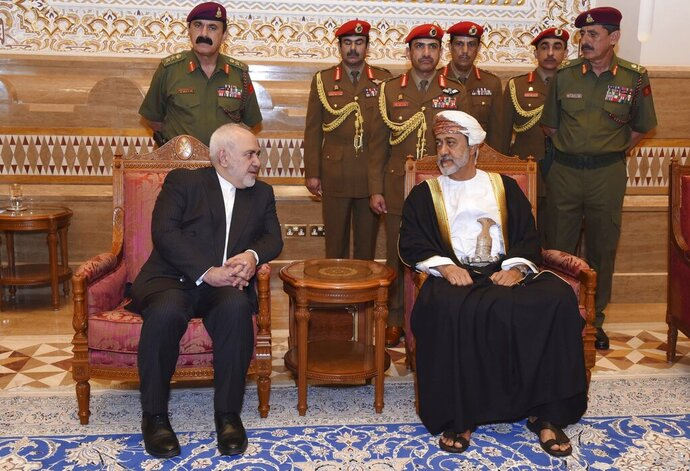 """In this Sunday, Jan. 12, 2020 photo, made available by the Oman News Agency, Oman's new Sultan Haitham bin Tariq Al Said, right, receives Iranian Foreign Minister Javad Zarif, after his arrival to attend an official mourning ceremony for the late Sultan Qaboos, in Muscat, Oman. A flurry of diplomatic visits and meetings crisscrossing the Persian Gulf are driving urgent efforts to defuse the possibility of all-out war after the U.S. killed Iran's top military commander. Global leaders and top diplomats are repeating in recent days the mantra of """"de-escalation"""" and """"dialogue,"""" yet none have publicly laid out a path to achieving either. (Oman News Agency via AP)"""