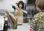 In this June 17, 2019, photo, a salesclerk puts goods into a paper bag after a customer purchased them, at a Seven-Eleven store in Yokohama, near Tokyo. Seven & i Holdings Co., a major Japanese convenience store operator, announced on May, 2019, a plan to replace all plastic shopping bags with paper by 2030 and all plastic packaging with paper, biodegradable or other reusable materials at its nearly 21,000 stores nationwide. Japan, as host of the Group of 20 Summit this weekend, hopes to lead the world in reducing plastic waste. (AP Photo/Koji Sasahara)