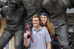 In this March 12, 2021, photo, Micah Shackel poses for pictures at the War Hymn Monument with her fiance, Josh Dickens, following a Texas A&M University makeup graduation ceremony for spring and summer 2020 graduates, at Kyle Field in College Station, Texas. Scores of campuses around the U.S. are offering last year's graduates a chance to experience the in-person commencements they missed out on when the pandemic upended life, Some are inviting them to join in festivities for the Class of 2021, while others are hosting separate commencements for them this spring or special events later this year.(Michael Miller/College Station Eagle via AP)
