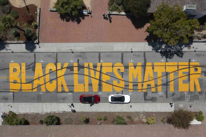 In this aerial photo provided by the Santa Cruz Police Department is a Black Lives Matter Mural painted on a street that was vandalized in Santa Cruz, Calif., on Saturday, July 24, 2021. Police in Northern California have arrested two men over allegedly vandalizing the mural. The mural had recently been repainted in celebration of Juneteenth, the Santa Cruz Sentinel reported Sunday, July 25, 2021. (Santa Cruz Police Department via AP)