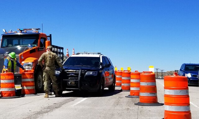 This photo provided by Patrick Sandoval shows authorities cordon off sections of the roadway in Gallup in Gallup, N.M., on Friday, May 1, 2020. Gov. Michelle Lujan Grisham invoked the state's Riot Control Act on Friday as she sealed off all roads to nonessential traffic in one of the largest communities bordering the Navajo Nation, where a surging coronavirus outbreak has already prompted widespread restrictions and weekend lockdowns. (Patrick Sandoval via AP)