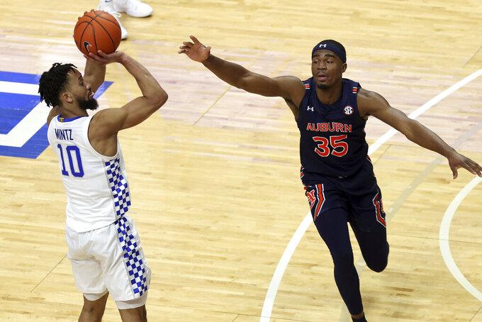 Kentucky's Davion Mintz takes a 3-point shot over Auburn's Devan Cambridge (35) late in the second half of an NCAA college basketball game in Lexington, Ky., Saturday, Feb. 13, 2021. Kentucky won 82-80. (AP Photo/James Crisp)