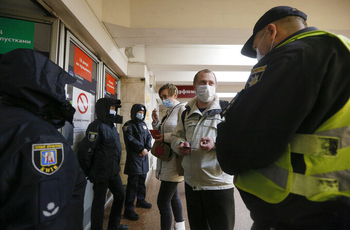 Policemen check the passenger passes at a subway station entrance in Kyiv, Ukraine, Monday, April 5, 2021. Authorities in Kyiv introduced tighter lockdown restrictions following a recent spike in virus cases. (AP Photo/Efrem Lukatsky)