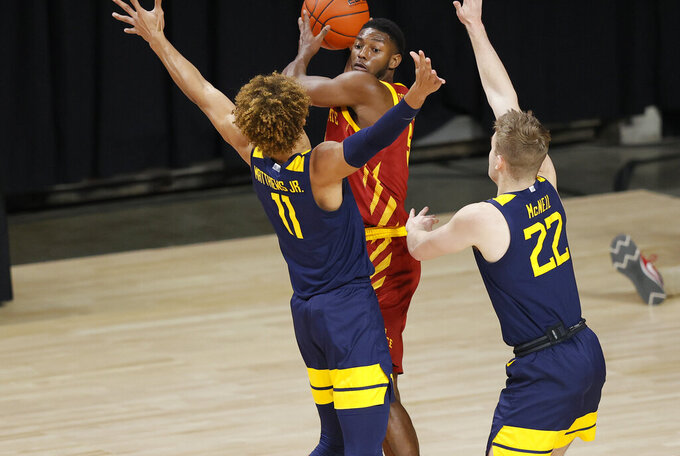 Iowa State guard Jalen Coleman-Lands, center, looks for a pass as he is defended by West Virginia forward Emmitt Matthews, left, and guard Sean McNeil, right, during the first half of an NCAA college basketball game, Tuesday, Feb. 2, 2021, in Ames, Iowa. (AP Photo/Matthew Putney)