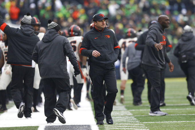 Oregon State head coach Jonathan Smith keeps an eye on the scoreboard during the first half of an NCAA college football game in Eugene, Ore., Saturday, Nov. 30, 2019. (AP Photo/Amanda Loman)
