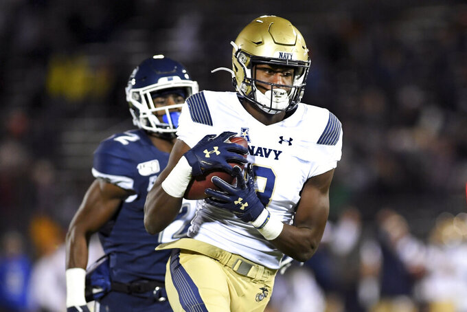 Navy wide receiver Myles Fells (23) gains yardage during the first half of the team's NCAA college football game against Connecticut on Friday, Nov. 1, 2019, in East Hartford, Conn. (AP Photo/Stephen Dunn)