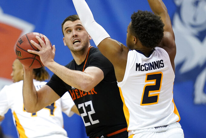 Mercer forward Felipe Haase (22) looks to pass around UNC-Greensboro guard A.J. McGinnis (2) in the first half of an NCAA men's college basketball championship game for the Southern Conference tournament, Monday, March 8, 2021, in Asheville, N.C. (AP Photo/Kathy Kmonicek)