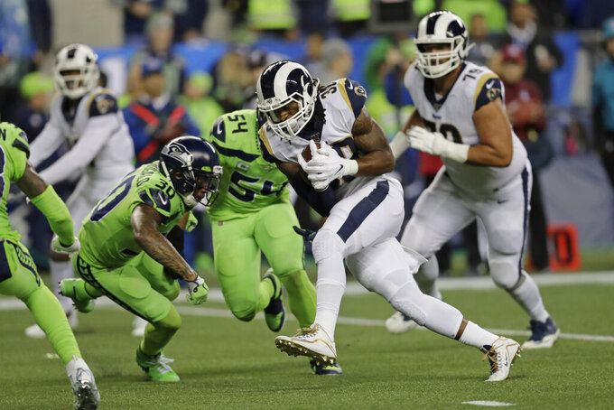 Los Angeles Rams running back Todd Gurley, second from right, rushes for a touchdown against the Seattle Seahawks during the second half of an NFL football game Thursday, Oct. 3, 2019, in Seattle. (AP Photo/Stephen Brashear)