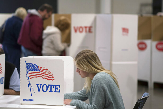 FILE - In this Nov. 8, 2016, file photo, a woman votes with others at an Edmond, Okla., church. Oklahoma election officials say registered independents will be able to continue voting in Democratic primaries during the next election cycle. (AP Photo/J Pat Carter, File)