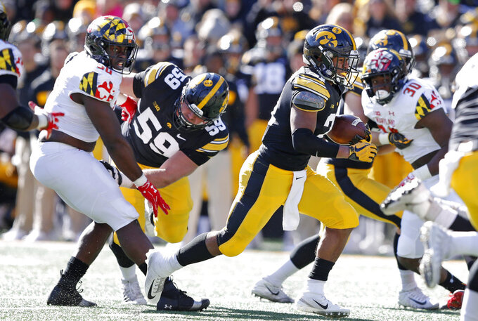 Iowa running back Ivory Kelly-Martin, right, carries the ball up field during the second half of an NCAA college football game against Maryland, Saturday, Oct. 20, 2018, in Iowa City, Iowa. Iowa won 23-0. (AP Photo/Charlie Neibergall)