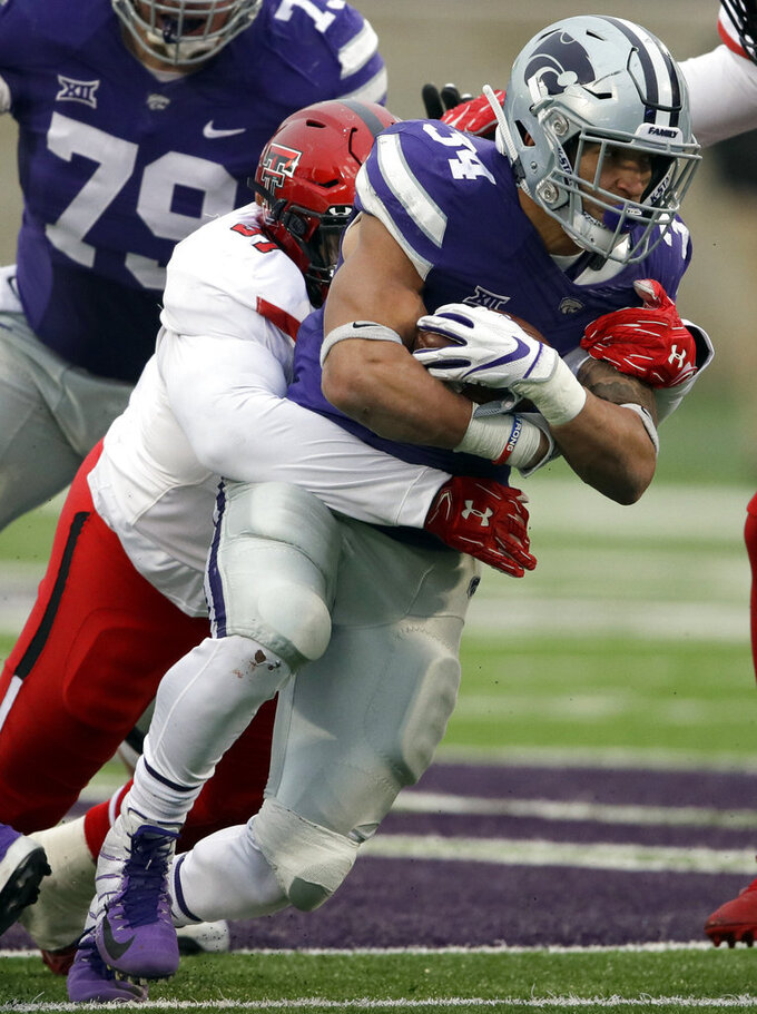Kansas State running back Alex Barnes (34) is tackled by Texas Tech defensive lineman Joseph Wallace (97) during the first half of an NCAA college football game in Manhattan, Kan., Saturday, Nov. 17, 2018. (AP Photo/Orlin Wagner)