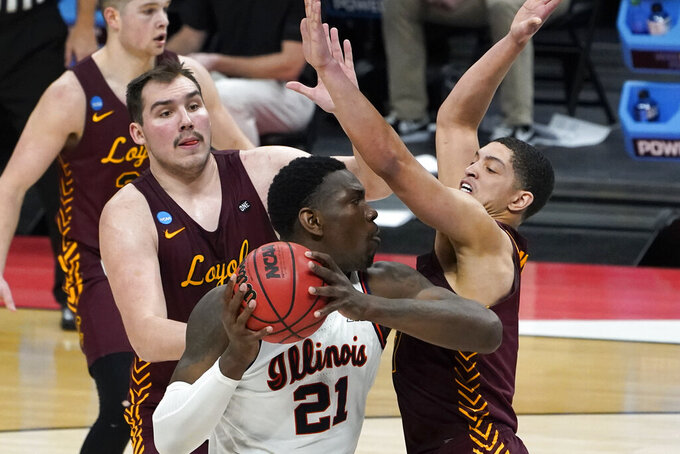 Illinois center Kofi Cockburn (21) is defended by Loyola Chicago center Cameron Krutwig, left, and Lucas Williamson, right, during the first half of a men's college basketball game in the second round of the NCAA tournament at Bankers Life Fieldhouse in Indianapolis, Sunday, March 21, 2021. (AP Photo/Paul Sancya)