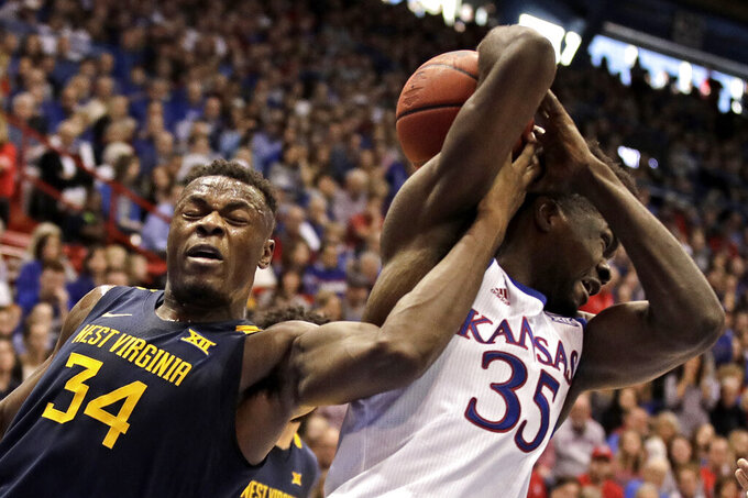 West Virginia's Oscar Tshiebwe (34) steals the ball from Kansas' Udoka Azubuike (35) during the first half of an NCAA college basketball game Saturday, Jan. 4, 2020, in Lawrence, Kan. (AP Photo/Charlie Riedel)