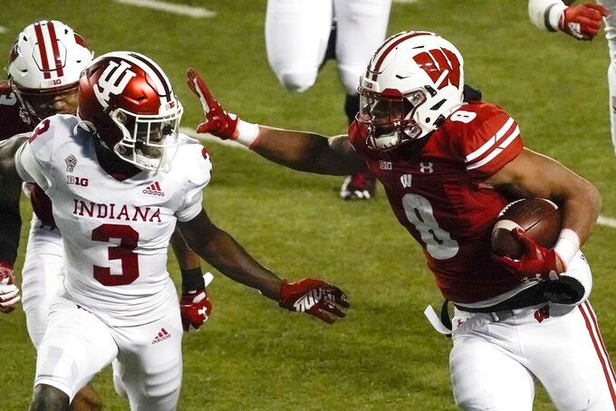 Wisconsin running back Jalen Bergertries to get past Indiana defensive back Tiawan Mullen during the second half of an NCAA college football game Saturday, Dec. 5, 2020, in Madison, Wis.Indiana won 14-6. (AP Photo/Morry Gash)