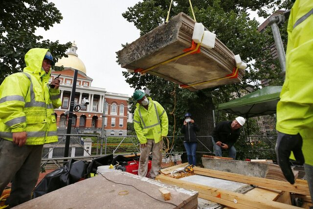 Workers inspect the top cornice stone as it is lifted from the Shaw 54th Regiment memorial opposite the Statehouse, Friday, July 17, 2020, in Boston. Amid the national reckoning on racism, the memorial to the first Black regiment of the Union Army, the Civil War unit popularized in the movie