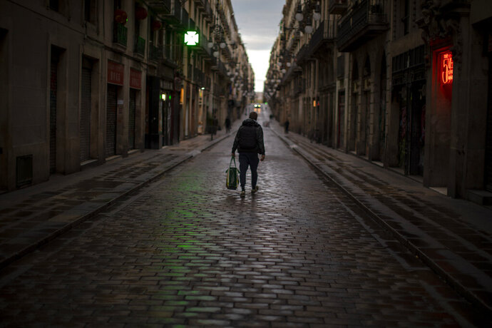 A man walks along an empty street in downtown Barcelona, Spain, Thursday, March 26, 2020 as the lockdown to combat the spread of coronavirus continues. The new coronavirus causes mild or moderate symptoms for most people, but for some, especially older adults and people with existing health problems, it can cause more severe illness or death. (AP Photo/Emilio Morenatti)
