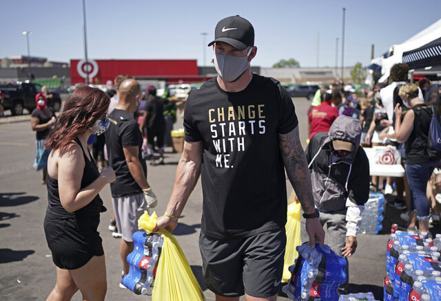 In this photo taken Friday, June 5, 2020, Minnesota Vikings NFL football player Kyle Rudolph helps a woman carry items to her car at the