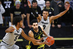 Oregon guard Ehab Amin, center, looks to pass the ball as Colorado guards D'Shawn Schwartz, left, and Shane Gatling defend during the second half of an NCAA basketball game Saturday, Feb. 2, 2019, in Boulder, Colo. Colorado won 73-51. (AP Photo/David Zalubowski)