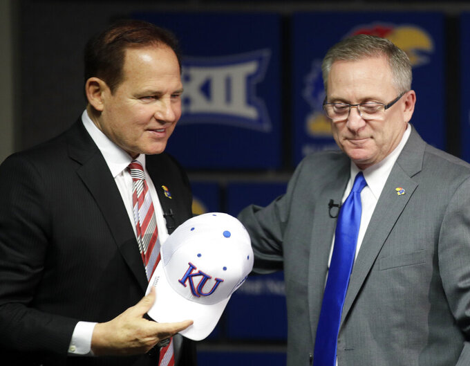 FILE - In this Nov. 18, 2018, file photo, Les Miles, left, is introduced as Kansas football coach by athletic director Jeff Long, right, during a news conference in Lawrence, Kan. Kansas has fired athletic director Jeff Long less than two days after mutually parting with Les Miles amid sexual misconduct allegations dating to the football coach's time at LSU, a person familiar with the decision told The Associated Press on Wednesday, March 10, 2021. (AP Photo/Orlin Wagner, File)