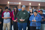 Community members attend a prayer vigil in the parking lot of the Bill Neal Center next to Channelview High School, Tuesday, March 13, 2018, in Channelview, Texas. The crash of a charter bus carrying a high school band from Florida to Texas left a driver dead and about three dozen people injured in south Alabama. (Mark Mulligan/Houston Chronicle via AP)