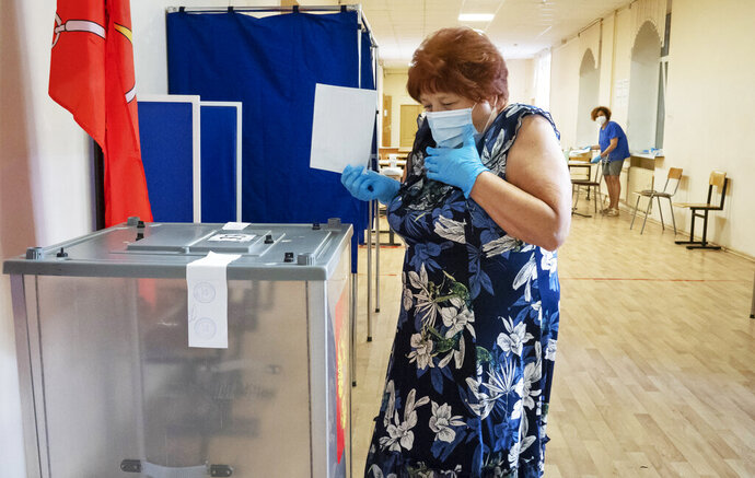 A voter wearing a face mask and protective gloves to protect against coronavirus walks to cast her ballot at a polling station in St.Petersburg, Russia, Thursday, June 25, 2020. Polls have opened in Russia on Thursday for a week-long vote on a constitutional reform that may allow President Vladimir Putin to stay in power until 2036. (AP Photo/Dmitri Lovetsky)