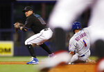 Miami Marlins shortstop Miguel Rojas (19) forces out New York Mets' Amed Rosario (1) at second base during the third inning of a baseball game on Friday, July 12, 2019, in Miami. Jason Vargas was out at first on the double play. (AP Photo/Brynn Anderson)