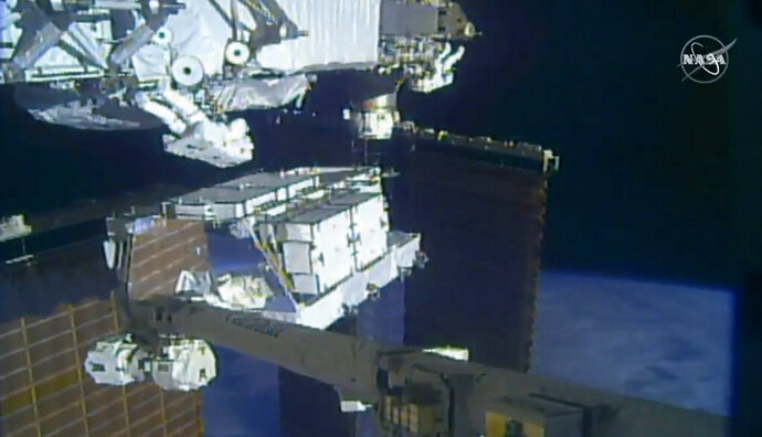In this image made from video provided by NASA, NASA astronauts Christina Koch and Andrew Morgan work outside the International Space Station, Sunday, Oct. 6 2019.  The astronauts kicked off the first of five spacewalks to replace old batteries at the International Space Station on Sunday. (NASA via AP)