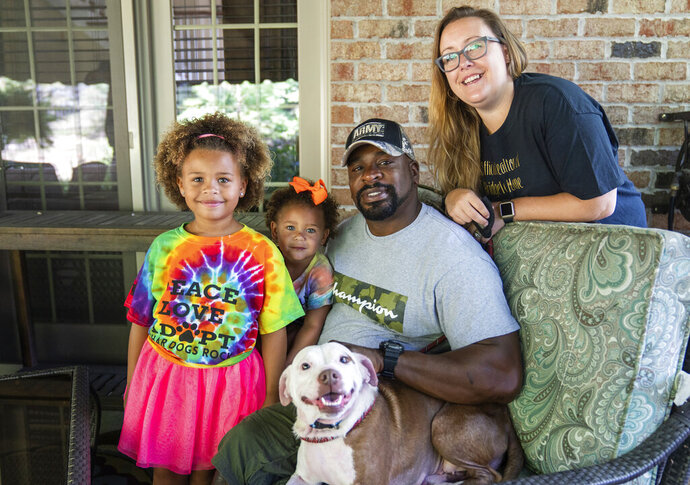 From left, Zaida Brooks, 5, Waverly Brooks, 2, their father, Omar Brooks, and mother, Nicole Malesic, pose for a photo with Maisie Mae, a foster dog at Bridge To Home Animal Rescue on Monday, July 6, 2020, in Eighty Four, Pa. Brooks and his family have been fostering dogs for the past two years. (Andrew Rush/Pittsburgh Post-Gazette via AP)