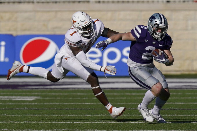 Texas defensive back Chris Adimora (1) catches up with Kansas State running back Harry Trotter (2) during the second half of an NCAA college football game in Manhattan, Kan., Saturday, Dec. 5, 2020. (AP Photo/Orlin Wagner)