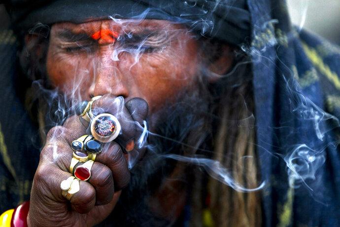FILE - In this March 4, 2019, file photo, a Hindu holy man smokes marijuana at the courtyard of the Pashupatinath Temple during Shivaratri festivalin Kathmandu, Nepal. Dozens of Nepalese parliament members have filed a proposal seeking to legalize marijuana use in the Himalayan nation. (AP Photo/Niranjan Shrestha, File)