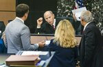 Holding up a copy of the application for the search warrant, Judge Leonard Hanser holds a bench conference with attorneys during a motion hearing in the Robert Kraft's case in West Palm Beach, Fla., Friday, April 26, 2019. (Lannis Waters/Palm Beach Post via AP)