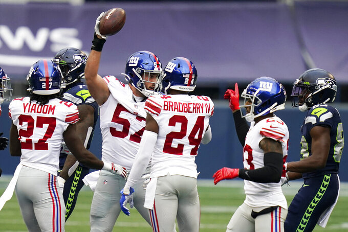 New York Giants defensive end Niko Lalos (57) celebrates with teammates after he recovered a fumble by Seattle Seahawks quarterback Russell Wilson (not shown) during the first half of an NFL football game, Sunday, Dec. 6, 2020, in Seattle. (AP Photo/Elaine Thompson)