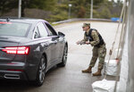 A member of the Rhode Island National Guard Military Police talks with a motorist with New York license plates at a checkpoint on I-95 near the border with Connecticut where New Yorkers must pull over and provide contact information and are told to self-quarantine for two weeks, Saturday, March 28, 2020, in Hope Valley, R.I. Rhode Island Gov. Gina Raimondo on Saturday ordered anyone visiting the state to self-quarantine for 14 days and restricted residents to stay at home and nonessential retail businesses to close Monday until April 13 to help stop the spread of the coronavirus. (AP Photo/David Goldman)