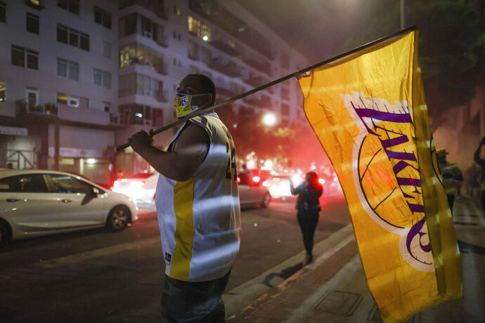 A Los Angeles Lakers fan celebrates outside of Staples Center after the Lakers defeated the Miami Heat in Game 6 of basketball's NBA Finals to win the championship. (AP Photo/Christian Monterrosa)