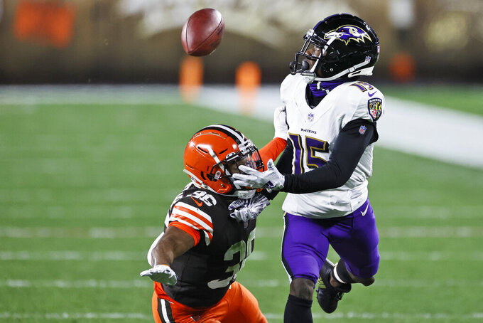 Baltimore Ravens wide receiver Marquise Brown (15) can't get to the ball under pressure from Cleveland Browns cornerback M.J. Stewart Jr. (36) during the first half of an NFL football game, Monday, Dec. 14, 2020, in Cleveland. Stewart was called for pass interference on the play. (AP Photo/Ron Schwane)