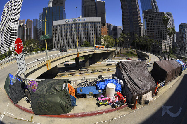 A homeless encampment is seen at the corner of Wilshire Blvd. and Beaudry Ave. as traffic moves along the 110 freeway below during the coronavirus outbreak, Thursday, May 21, 2020, in downtown Los Angeles. (AP Photo/Mark J. Terrill)