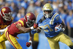 UCLA running back Joshua Kelley (27) rushes as Southern California linebacker John Houston Jr. (10) tugs on his jersey during the first half of an NCAA college football game Saturday, Nov. 17, 2018, in Pasadena, Calif. (AP Photo/Marcio Jose Sanchez)