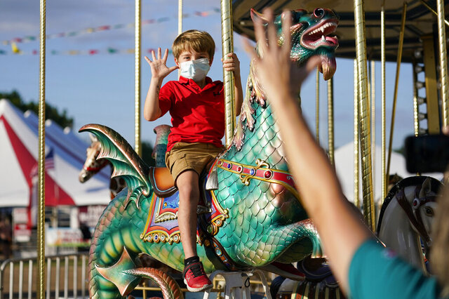 A masked Giles Parish, 7, waves to his aunt Pam Tompkins of Vicksburg, Miss., as he rides the merry-go-round at the Mississippi State Fair in Jackson, Miss., Wednesday, Oct. 7, 2020. The fair's grand opening went ahead as planned amid criticism that masks will not be required at the event after Gov. Tate Reeves repealed the state's mask mandate. However, the state agriculture commissioner had boxes of face masks at each entrance for those who wanted one. (AP Photo/Rogelio V. Solis)