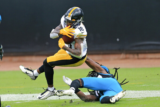 Pittsburgh Steelers wide receiver Diontae Johnson, left, makes a reception despite defensive effort by Jacksonville Jaguars cornerback Tre Herndon, right, during the first half of an NFL football game, Sunday, Nov. 22, 2020, in Jacksonville, Fla. (AP Photo/Matt Stamey)